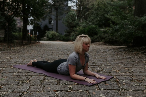 Woman doing yoga outside sphinx pose | 11 Beginner-Approved Yoga Exercises to Boost Your Day