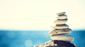 stacked rocks near ocean | What is Wellness and How to Make It Work for You https://positiveroutines.com/wellness-definition/