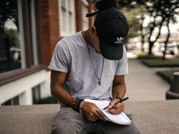 black man writing | How to Define Gratitude + Have a Better Holiday Season https://positiveroutines.com/define-gratitude/