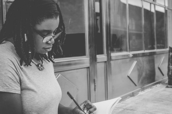 black woman writing in notebook   7 Quotes About Goals that Will Keep You Moving