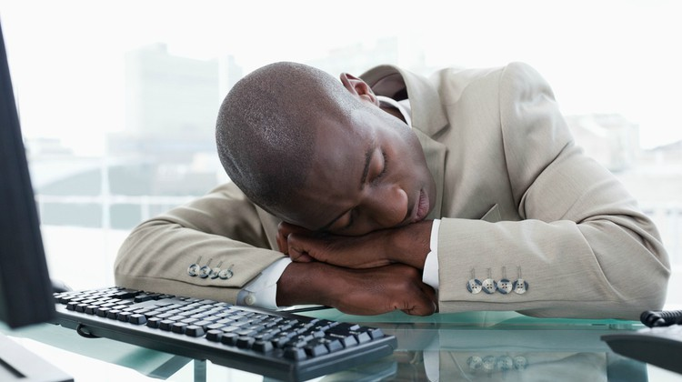 black man in suit asleep at work | Why Sleep is Key to Increasing Productivity