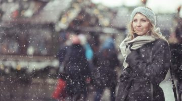 woman standing outside in snow in a city | 54 Ways to Be Happy That Will Reverse the Winter Blues https://positiveroutines.com/ways-to-be-happy/ ‎