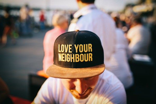 man wearing hat that says love your neighbor | The Research-Backed to Money and Happiness