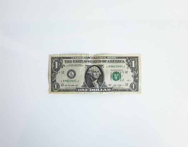 one US dollar on white background | The Research-Backed Guide to Money and Happiness
