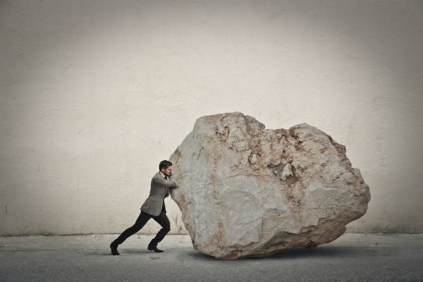 businessman pushing giant rock | 72 Resources to Overcome Procrastination and Improve Productivity https://positiveroutines.com/overcome-procrastination-resources/