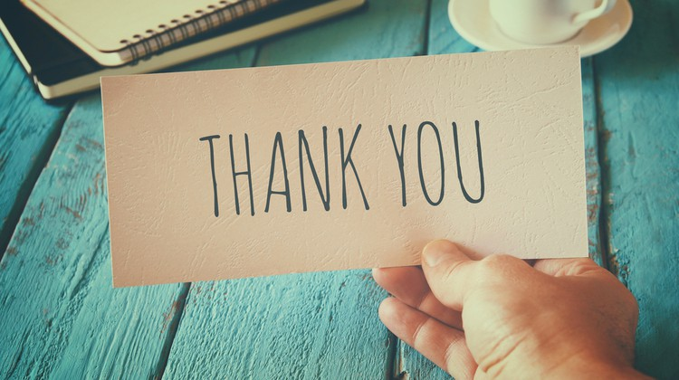 mans hand holding thank you note   10 Expert-Approved Gratitude Messages for Mom