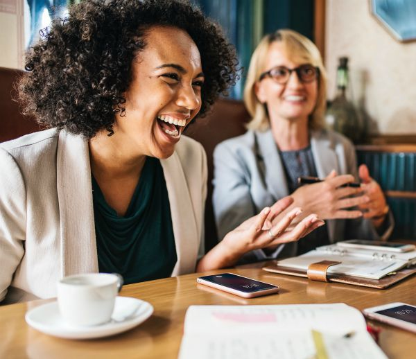 black woman laughing and talking to coworkers | 3 Expert Secrets to Relationship Building https://positiveroutines.com/relationship-building-secrets/