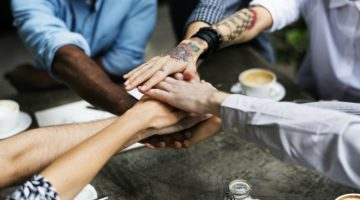 diverse group of hands piled together relationship building concept | 3 Expert Secrets to Relationship Building  https://positiveroutines.com/relationship-building-secrets/