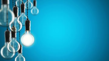 vintage lightbulbs hanging from ceiling one lit up leadership concept | The Best Ted Talks on Leadership to Inspire You Today https://positiveroutines.com/best-ted-talks-leadership/