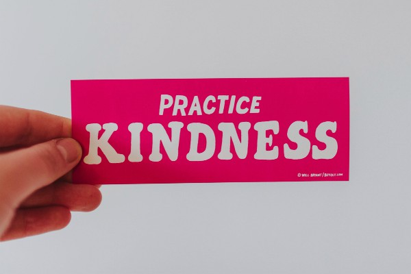 hand holding sign says practice kindness | Why You Need to Try Loving-Kindness Meditation https://positiveroutines.com/loving-kindness-meditation/