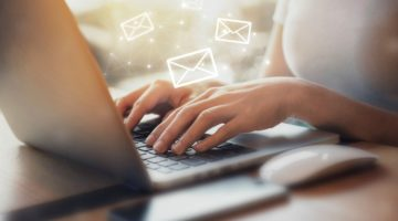 woman typing on laptop with email symbols | 5 Productivity Hacks for Ultimate Email Efficiency https://positiveroutines.com/productivity-hacks-email/ ‎