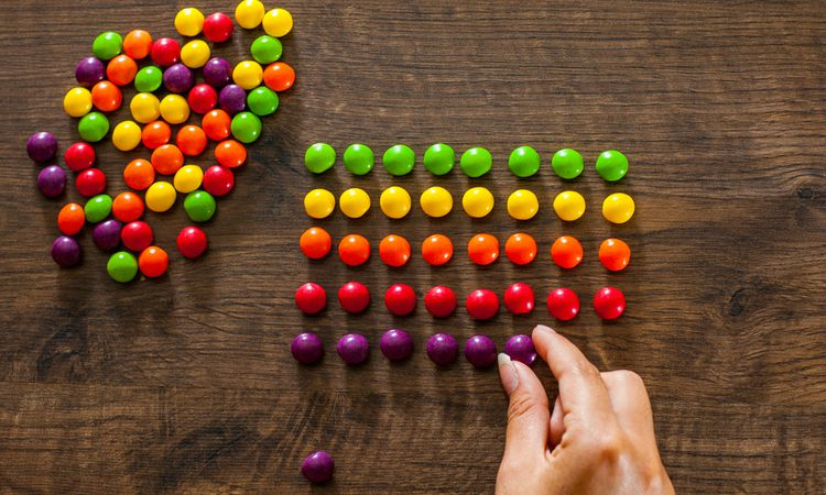 woman organizing candies into perfect rows perfectionism concept | How to Make Being a Perfectionist Work For You  https://positiveroutines.com/being-a-perfectionist/