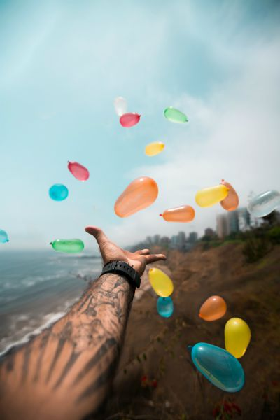 tattooed arm releasing colorful balloons near ocean | Why is Finding Meaning In Life and Work So Important? https://positiveroutines.com/finding-meaning/