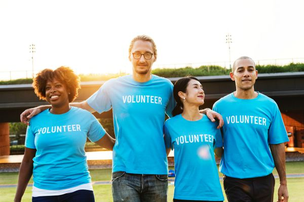 diverse colleagues with arms around each other volunteer | For Ultimate Productivity, Manage Your Energy, Not Your Time  https://positiveroutines.com/manage-your-energy-not-your-time/