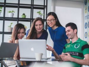 group of young people looking at computer screen | 7 Surprising Ways to Be Successful at Work https://positiveroutines.com/successful-at-work/