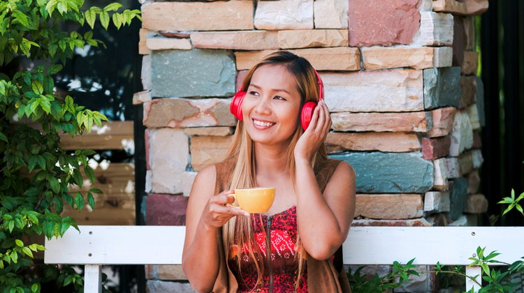 female with red headphones enjoying tea | The Most Inspirational Podcasts of 2018 https://positiveroutines.com/inspirational-podcasts/