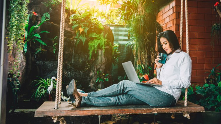 female relaxing on outdoor swing using laptop | How to Work Remotely + Why You Should Try It This Year https://positiveroutines.com/how-to-work-remotely/