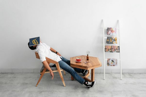 lazy man slouched in chair covering face with book | Productive Procrastination Exists. Here's How To Do It. https://positiveroutines.com/productive-procrastination/