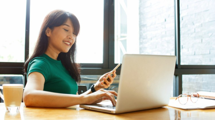 productive woman smiling while using laptop and smartphone | Productive Procrastination Exists. Here's How To Do It. https://positiveroutines.com/productive-procrastination/
