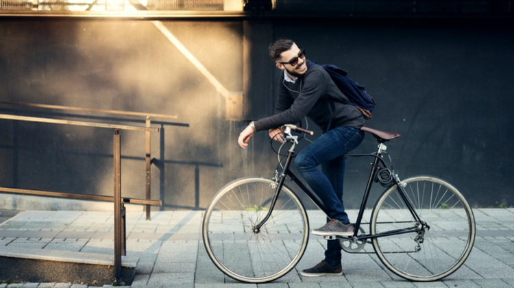 happy male commuter on bicycle | How to Take Advantage of a Flexible Schedule https://positiveroutines.com/flexible-schedule-tips/