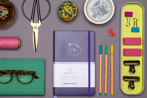 purple panda planner on desk with other supplies | 7 Easy Ways to Build a More Positive Mindset https://positiveroutines.com/positive-mindset/