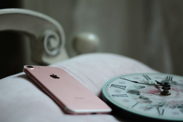 rose gold iphone laying beisde floral analog clock | How to Take Advantage of a Flexible Schedule https://positiveroutines.com/flexible-schedule-tips/