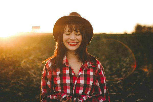 smiling woman in red flannel shirt | 13 Gratitude Journal Prompts to Try This International Day of Happiness https://positiveroutines.com/gratitude-journal-prompts/