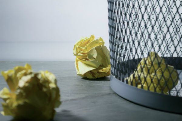 "crumpled paper sitting outside of wastebasket | How to Stop Feeling Guilty For Not Getting ""Enough"" Work Done https://positiveroutines.com/stop-feeling-guilty/"