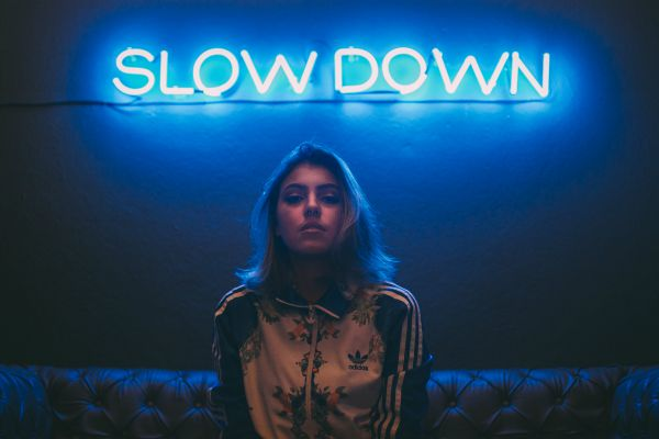 "woman with neon sign says slow down | How to Stop Feeling Guilty For Not Getting ""Enough"" Work Done https://positiveroutines.com/stop-feeling-guilty/"