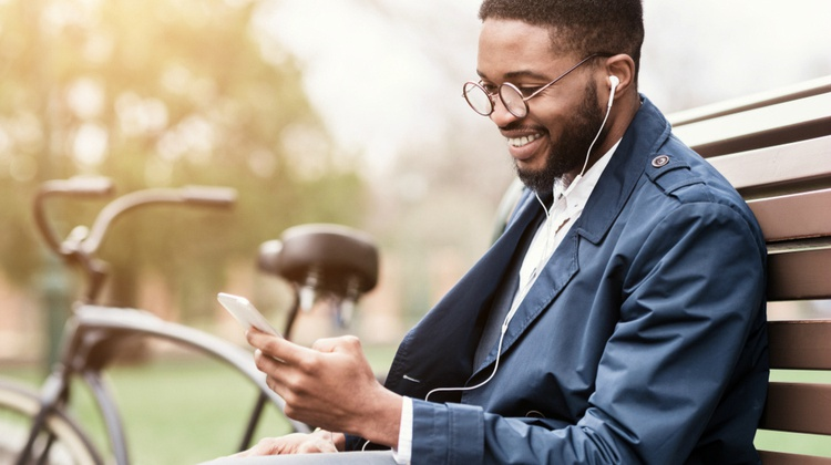 happy-male-on-park-bench-wearing-earbuds | 13 Ways to be Happier This Summer https://positiveroutines.com/be-happier-this-summer/