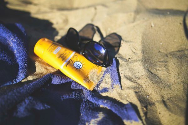 sunglasses and sunscreen in sand   This is Why We're Happier in Summer https://positiveroutines.com/happier-in-summer
