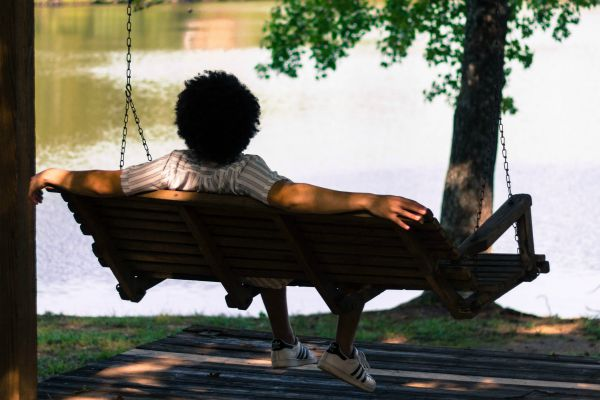 person relaxing on wooden bench swing | Is Work and Life Balance Even Achievable in 2019? https://positiveroutines.com/work-and-life-balance-tips/