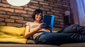 happy woman reading book in evening | The Happiness-Boosting Magic of Evening Routines https://positiveroutines.com/evening-routines/